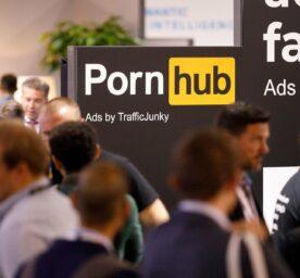 Logo of the Canadian erotic video platform Pornhub at a trade fair, men walking by
