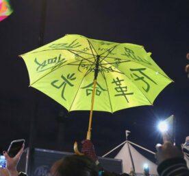 Hong Kong Democracy Protest at Trafalgar Square London. A protestor holds up high a yellow umbrella.