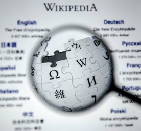 Wikipedia Logo under a magnifying glass