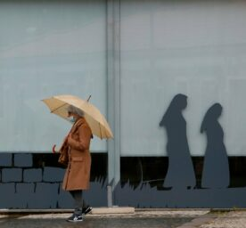 A woman wearing a face mask walks past closed shops in Fatima, Portugal, Tuesday, May 12, 2020.