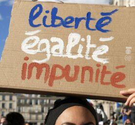 French feminist activists protest. Sign reads: liberté, egalité, impunité