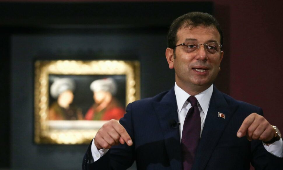 Istanbul Mayor Ekrem Imamoglu in front of a painting by Gentile Bellini which depicts Fatih Sultan Mehmet II alongside a man whose identity is unknown.