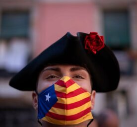 A man with wearing a mask with a Catalonian flag.