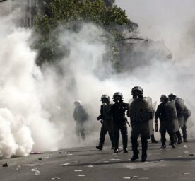 Riot police officers clash with protesters