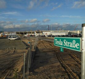 """View of the street sign """"Tesla Street 1"""" in front of the construction site of the Tesla factory."""