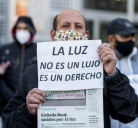 A protester is displaying a placard demanding a solution to the problem of the lack of electricity in la Cañada Real, Madrid