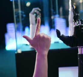 An employee demonstrates a wearable AI-powered bionic hand at the JD Global Technology Discovery Conference in Beijing, lifting a finger