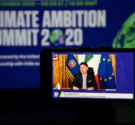 """Man sits in front of """"Climate Ambition Summit 2020"""" backdrop and flags"""