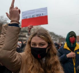 A woman wearing a protective face mask gestures a middle finger to police officers during an anti-government protest on December 13, 2020 in Warsaw, Poland.