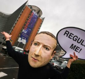 A campaigner wearing a mask of Zuckerberg