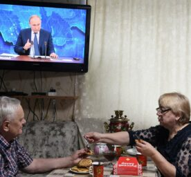 An elderly couple watches a TV broadcast showing the annual end-of-year news conference of Russian President Vladimir Putin.