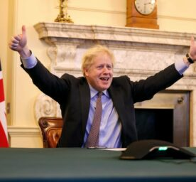 Man gives thumbs up in front of Union Jack flag