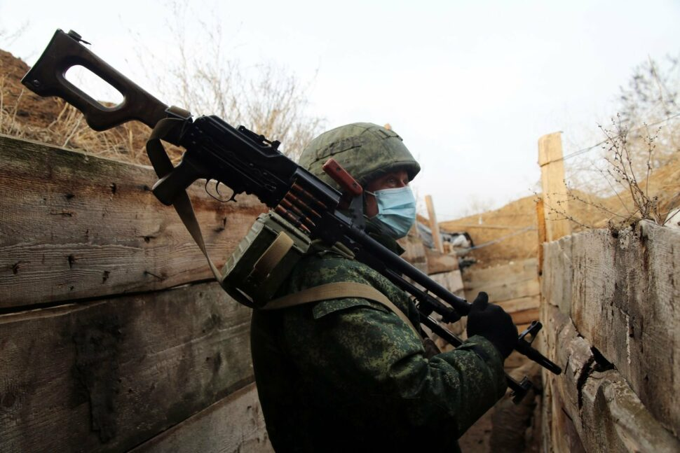 A serviceman of the People's Militia of the Donetsk People's Republic (DPR) holds a machine gun on a position near the village of Sakhanka, some 30 km east of Mariupol, the self-proclaimed Donetsk Peoples Republic, Eastern Ukraine.