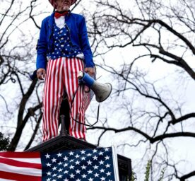 A Trumo supporter dressed in a Uncle Sam costume silently looks over the demonstration near the U.S. Capitol.