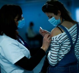 A nurse administrates a Pfizer / Biontech COVID-19 vaccine to a health care worker in Belgium