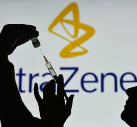 An illustrative image of a person holding a medical syringe and vale in front of the AstraZeneca logo displayed on a screen.