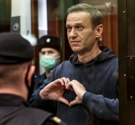 Russian opposition leader Alexei Navalny shows a heard symbol standing in the cage.