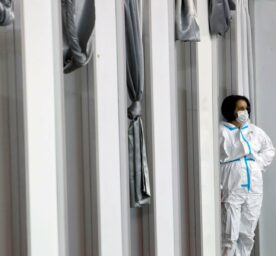A medical worker wearing protective gear waits for people to receive the COVID-19 vaccine, at Belgrade Fair makeshift vaccination center