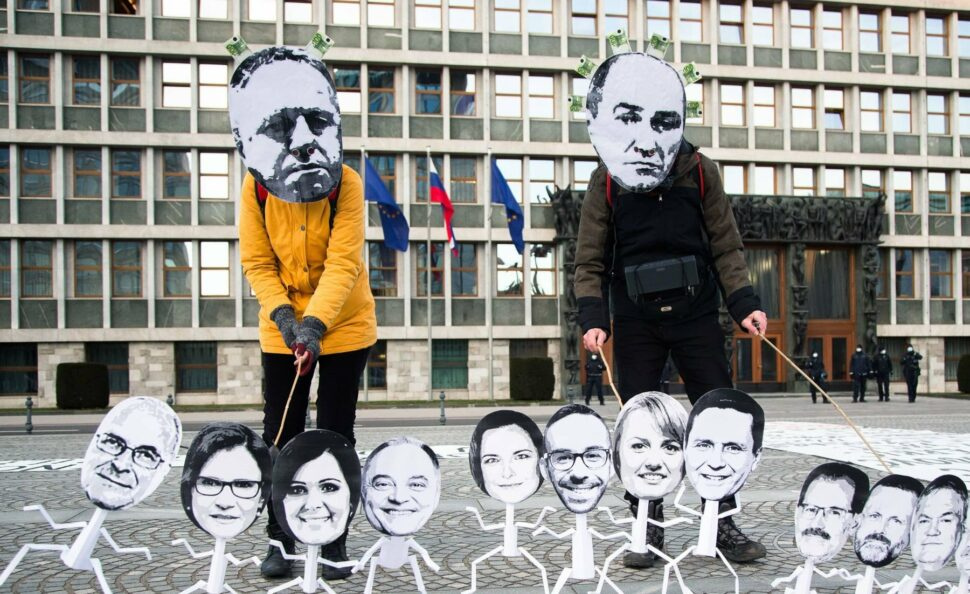 Protesters wearing a mask with Prime Minister Janez Jansa's and Minister of Economy Zdravko Pocivalsek's face hold paper figures of members of the parliament