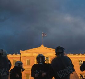 Greek riot police officers standing in front of the Hellenic Parliament