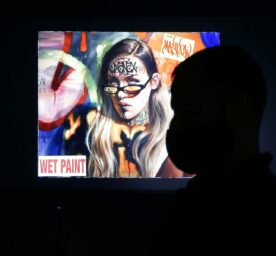 People walk through and look at the NFT works of art at a press preview and Grand opening of Superchief Gallery NFT, in New Tork City, March 25, 2021.