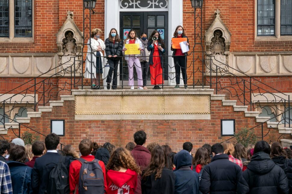 Female students holding signs standing on steps of a London school, crowd of male students listening below