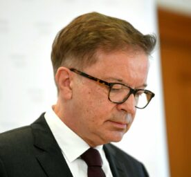 Health Minister Rudolf Anschober looks down while he is leaving his position