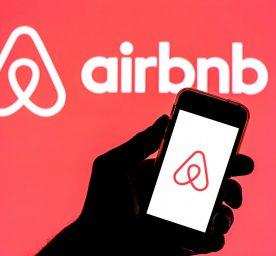 Phone with Airbnb logo in front of a bigger Airbnb logo