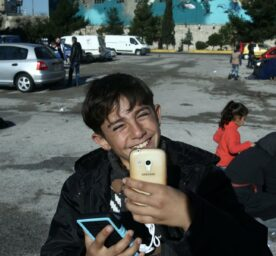 Young boy smiles and holds up a phone