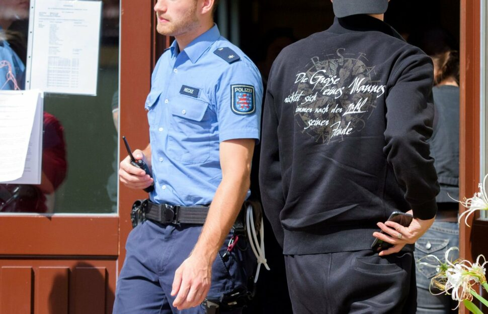 A defendant in Nazi clothes enters the community hall in Ballstädt (Thuringia) while a police officer steps out