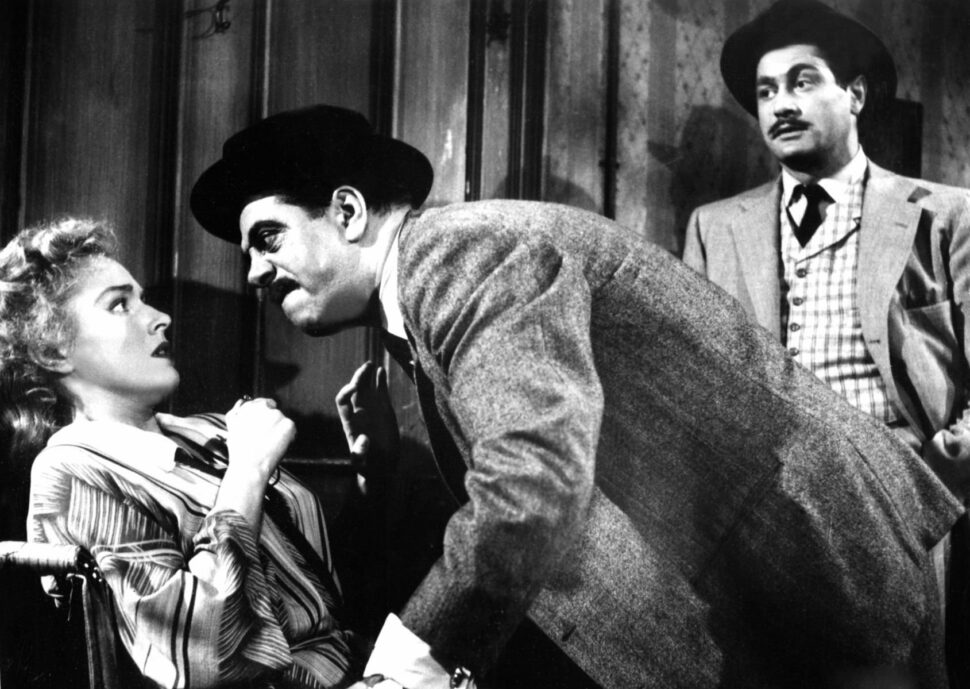 An angry man leans aggressively approaches a seated terrified woman, while another man casually looks on