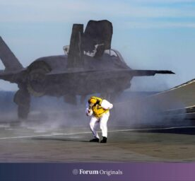 A Navy sailor reacts as a F-35B Lightning stealth fighter aircraft launches from the flight deck