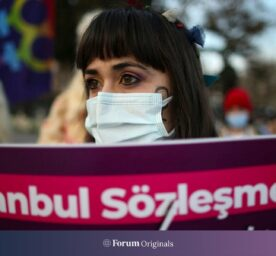 """A protester holds a placard reading in Turkish: """"Istanbul Convention', during a demonstration in Istanbul, Friday, April 2, 2021."""