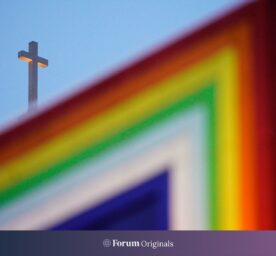 A rainbow colored sculpture is seen with a Cathohlic church cross in the background in Warsaw, Poland