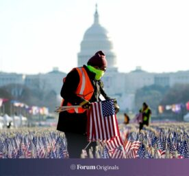Workers remove a display of flags on the National Mall one day after the inauguration of Joe Biden