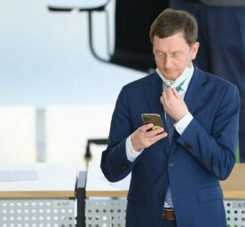 Saxony's prime minister Michael Kretschmer (CDU) is standing inside the state parliament. He is wearing a blue suit, is pulling his mask down and checking his phone.