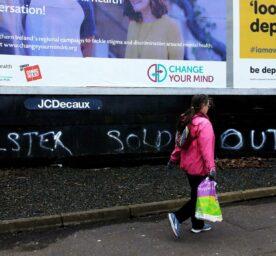 Woman walks past a graffiti
