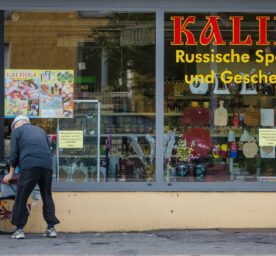 An elderly man stands with his bicycle in front of a Russian speciality shop in Ludwigsburg, Germany.