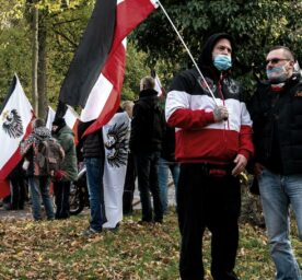 A far-right demonstrator carries a black and red flag. So-called Reichsbürger and other opponents are holding different flags