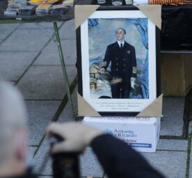 A man takes a picture of a painting of Franco.