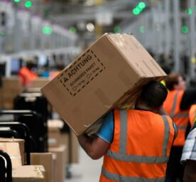 An employee carries a parcel in the logistics center of Amazon