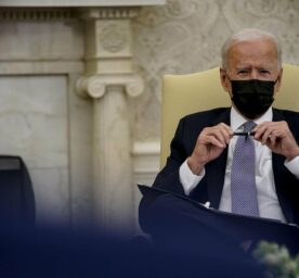 United States President Joe Biden meets with a bipartisan group of Members of Congress, holding a pen and looking fiercly