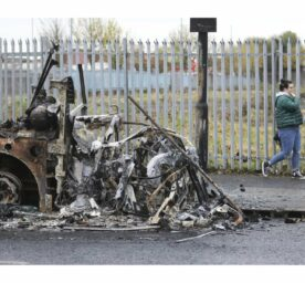 A woman walks past a burnt out bus on the Shankill road in West Belfast, Northern Ireland, Thursday, April 8, 2021.