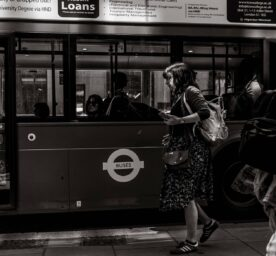 Woman walks by a London bus with a rucksack and bag