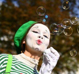 An artist blows soap bubbles