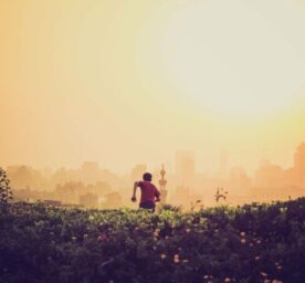 A boy runs from a meadow towards a city in heated atmosphere