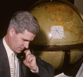 A man is on the phone, sitting in front of a globe.