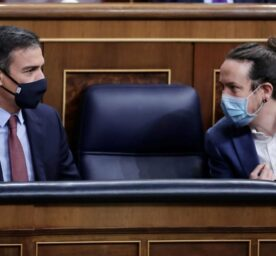 Prime Minister Pedro Sanchez, left and deputy Prime Minister Pablo Iglesias talk during a parliamentary session
