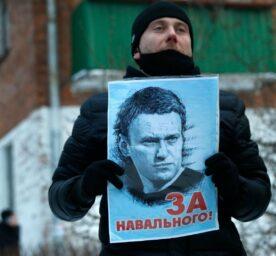 A protestor is holding up a portrait of Alexej Nawalny.