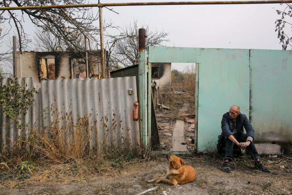 A man with his dog sits outside of his burnt to the ground yard in Syrotyno village, Luhansk region, Ukraine, October 2, 2020.
